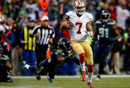 SEATTLE, WA - JANUARY 19: Quarterback Colin Kaepernick #7 of the San Francisco 49ers runs the ball as cornerback Richard Sherman #25 of the Seattle Seahawks attempts a tackle in the second quarter during the 2014 NFC Championship at CenturyLink Field on January 19, 2014 in Seattle, Washington.