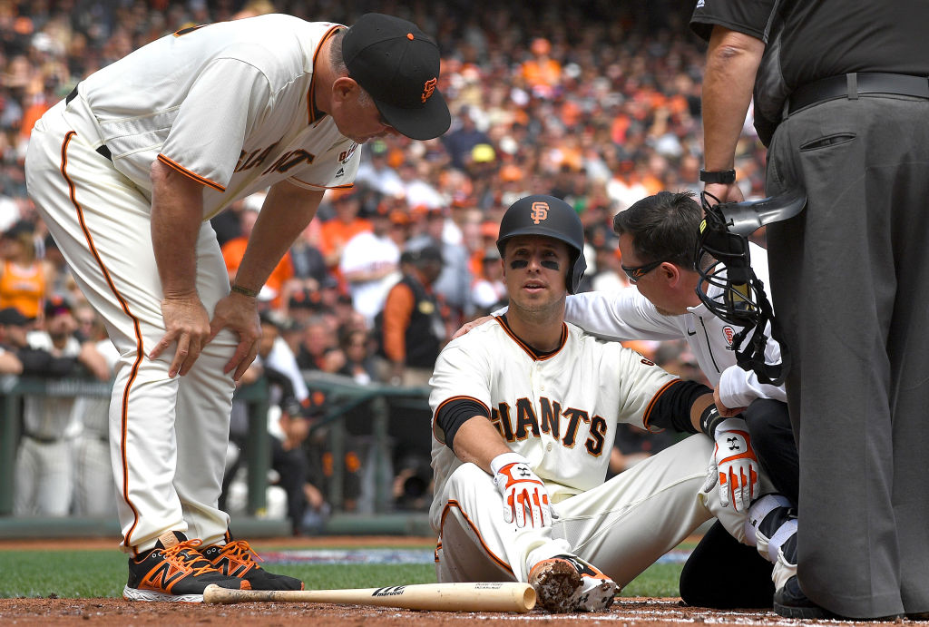 SAN FRANCISCO, CA - APRIL 10: Buster Posey #28 of the San Francisco Giants sits on the ground and is checked on by manger Bruce Bochy #15 and trainer Dave Groeschner after Posey was hit in the head with a pitch in the bottom of the first inning at AT&T Park on April 10, 2017 in San Francisco, California. Posey was taken out of the game after he was hit by the pitch.