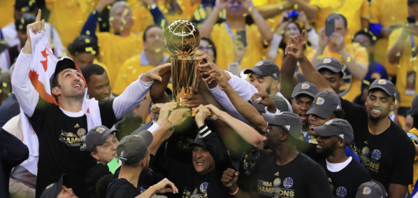 OAKLAND, CA - JUNE 12: The Golden State Warriors celebrate with the Larry O'Brien Championship Trophy after defeating the Cleveland Cavaliers 129-120 in Game 5 to win the 2017 NBA Finals at ORACLE Arena on June 12, 2017 in Oakland, California