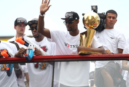 MIAMI, FL - JUNE 24: Forward Chris Bosh #1 of the Miami Heat holds the Larry O'Brien NBA Championship Trophy as he rides a bus during the championship victory parade on June 24, 2013 in Miami, Florida. The Miami Heat defeated the San Antonio Spurs in the NBA Finals