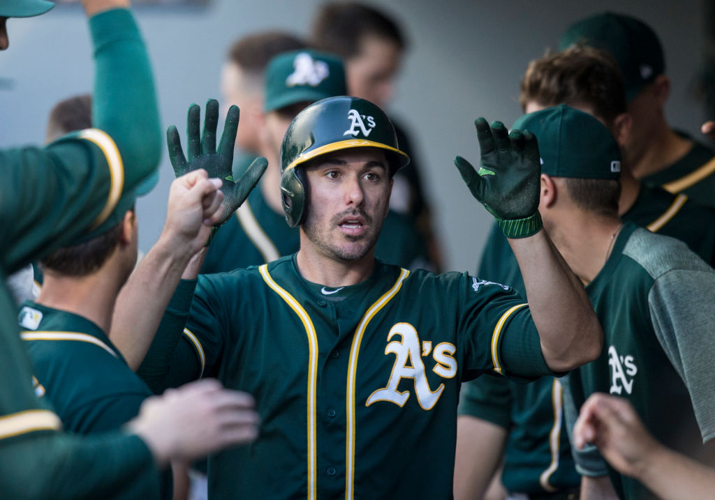 SEATTLE, WA - JULY 6: Matt Joyce #23 of the Oakland Athletics is congratulated by teammates in the dugout after scoring a run on a double by Yonder Alonso #17 of the Oakland Athletics off of starting pitcher Sam Gaviglio #44 of the Seattle Mariners during the first inning of a game at Safeco Field on July 6, 2017 in Seattle, Washington.