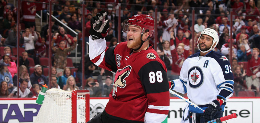 GLENDALE, AZ - JANUARY 13: Jamie McGinn #88 of the Arizona Coyotes celebrates after scoring a goal against Dustin Byfuglien #33 and the Winnipeg Jets during the first period of the NHL game at Gila River Arena on January 13, 2017 in Glendale, Arizona.