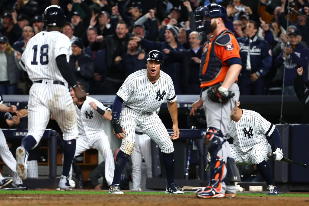 NEW YORK, NY - OCTOBER 17: Aaron Judge #99 of the New York Yankees celebrates as he and teammate Didi Gregorius #18 score on a two-run go-ahead double by Gary Sanchez #24 during the eighth inning against the Houston Astros in Game Four of the American League Championship Series at Yankee Stadium on October 17, 2017 in the Bronx borough of New York City.