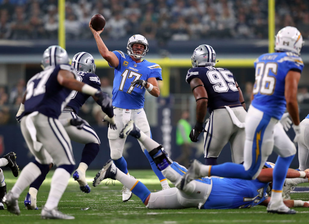 ARLINGTON, TX - NOVEMBER 23: Philip Rivers #17 of the Los Angeles Chargers passes under pressure from DeMarcus Lawrence #90 of the Dallas Cowboys and David Irving #95 of the Dallas Cowboys in the first half of a football game at AT&T Stadium on November 23, 2017 in Arlington, Texas