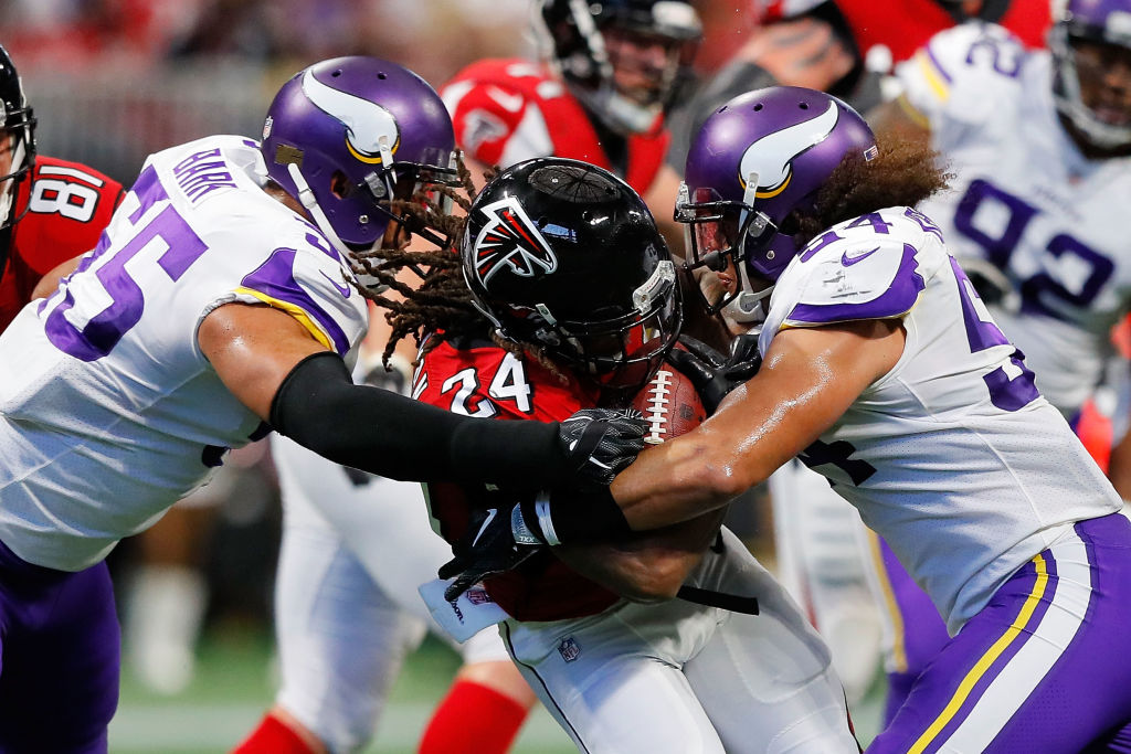 ATLANTA, GA - DECEMBER 03: Devonta Freeman #24 of the Atlanta Falcons is tackled by Eric Kendricks #54 and Anthony Barr #55 of the Minnesota Vikings during the first half at Mercedes-Benz Stadium on December 3, 2017 in Atlanta, Georgia.