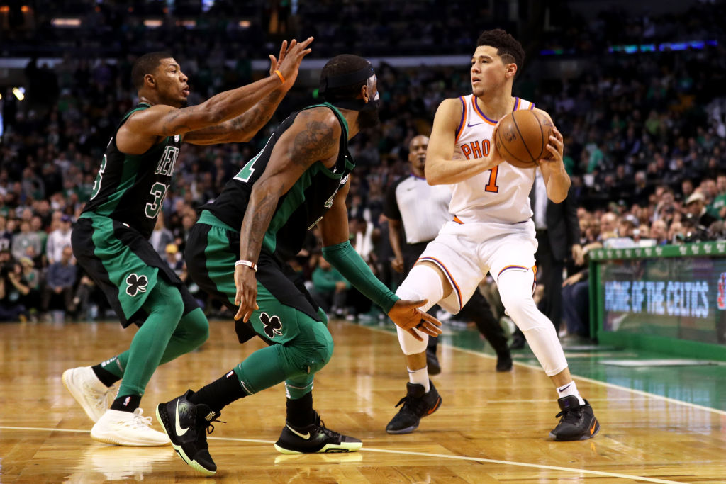 BOSTON, MA - DECEMBER 2: Kyrie Irving #11 of the Boston Celtics and Marcus Smart #36 defend Devin Booker #1 of the Phoenix Suns during the second half at TD Garden on December 2, 2017 in Boston, Massachusetts. The Celtics defeat the Suns 116-111.