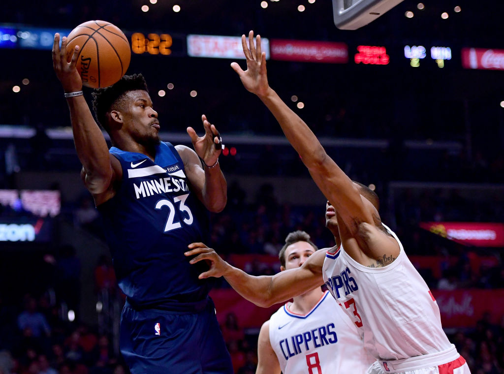 LOS ANGELES, CA - DECEMBER 06: Jimmy Butler #23 of the Minnesota Timberwolves passes around Wesley Johnson #33 and Danilo Gallinari #8 of the LA Clippers during the first half at Staples Center on December 6, 2017 in Los Angeles, California.