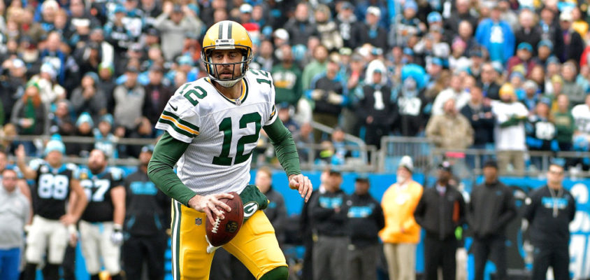 CHARLOTTE, NC - DECEMBER 17: Aaron Rodgers #12 of the Green Bay Packers runs with the ball against the Carolina Panthers in the second quarter during their game at Bank of America Stadium on December 17, 2017 in Charlotte, North Carolina.