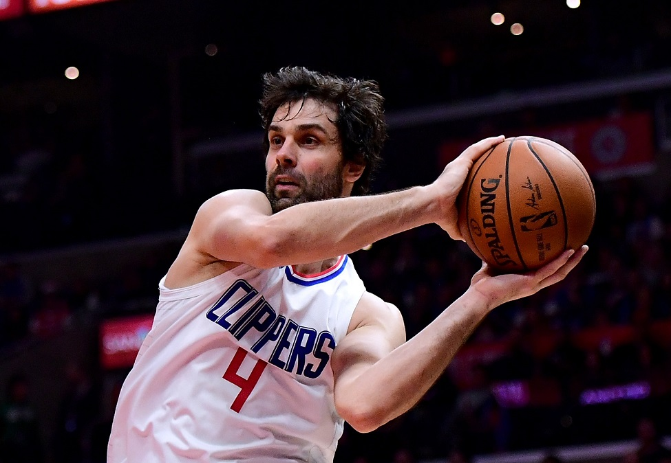 LOS ANGELES, CA - DECEMBER 20: Milos Teodosic #4 of the LA Clippers passes around Alan Williams #15 of the Phoenix Suns during the first half at Staples Center on December 20, 2017 in Los Angeles, California.