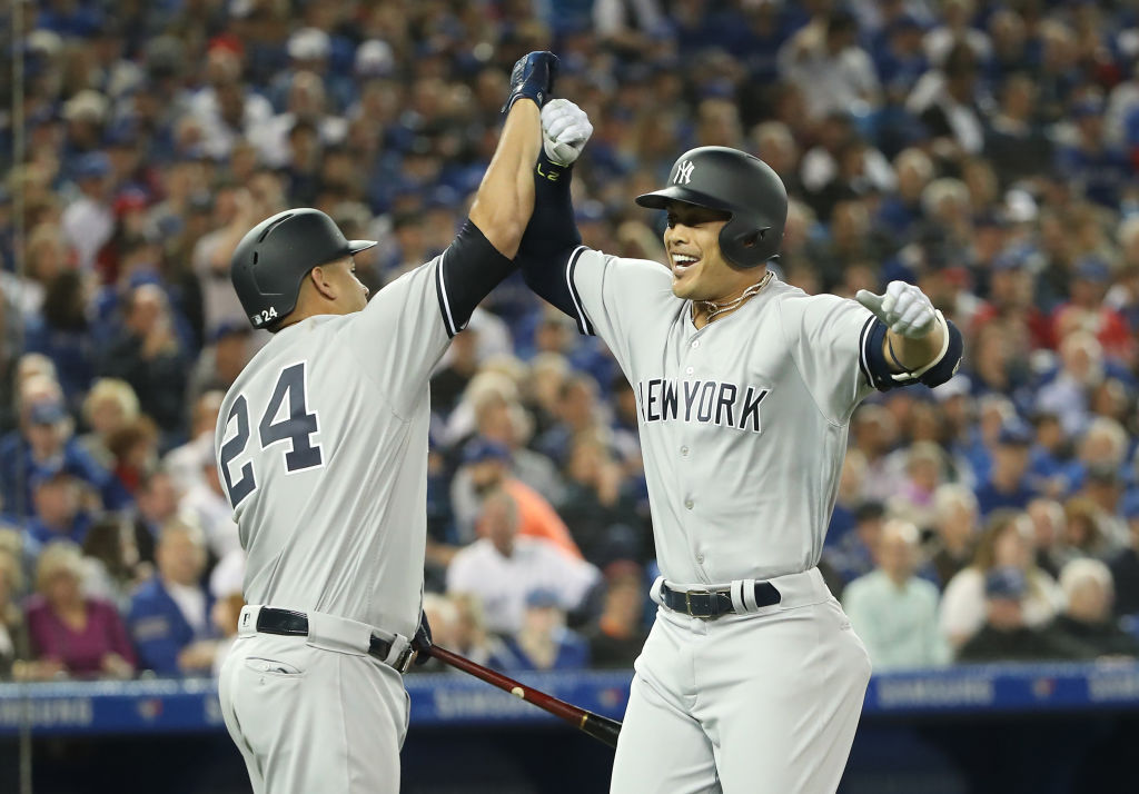 TORONTO, ON - MARCH 29: Giancarlo Stanton #27 of the New York Yankees is congratulated by Gary Sanchez #24 after hitting a two-run home run in the first inning on Opening Day during MLB game action against the Toronto Blue Jays at Rogers Centre on March 29, 2018 in Toronto, Canada.