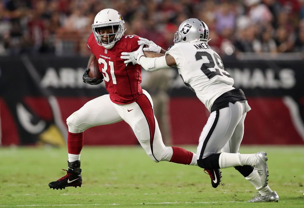 GLENDALE, AZ - AUGUST 12: Running back David Johnson #31 of the Arizona Cardinals rushes the football past cornerback David Amerson #29 of the Oakland Raiders during the NFL game at the University of Phoenix Stadium on August 12, 2017 in Glendale, Arizona. The Cardinals defeated the Raiders 20-10.