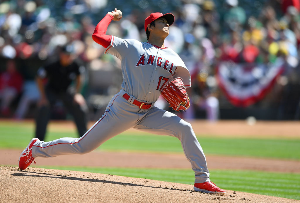 OAKLAND, CA - APRIL 01: Shohei Ohtani #17 of the Los Angeles Angels of Anaheim pitches in the bottom of the first inning of his Major League pitching debut against the Oakland Athletics at Oakland Alameda Coliseum on April 1, 2018 in Oakland, California.