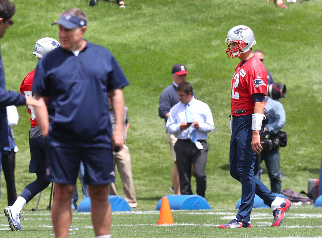 FOXBOROUGH, MA - JUNE 5: New England Patriots quarterback Tom Brady, right, walks on the field during a passing drill at Patriots minicamp as head coach Bill Belichick stands at foreground left at the Gillette Stadium practice facility in Foxborough, MA on June 5, 2018.