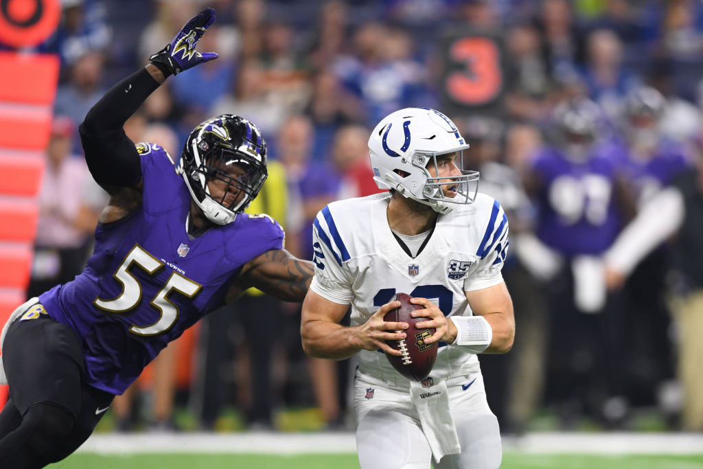 Indianapolis Colts quarterback Andrew Luck (12) holds onto the football as Baltimore Ravens linebacker Terrell Suggs (55) tackles him from behind in action during the preseason NFL game between the Indianapolis Colts and the Baltimore Ravens on August 20, 2018 at Lucas Oil Stadium in Indianapolis, Indiana