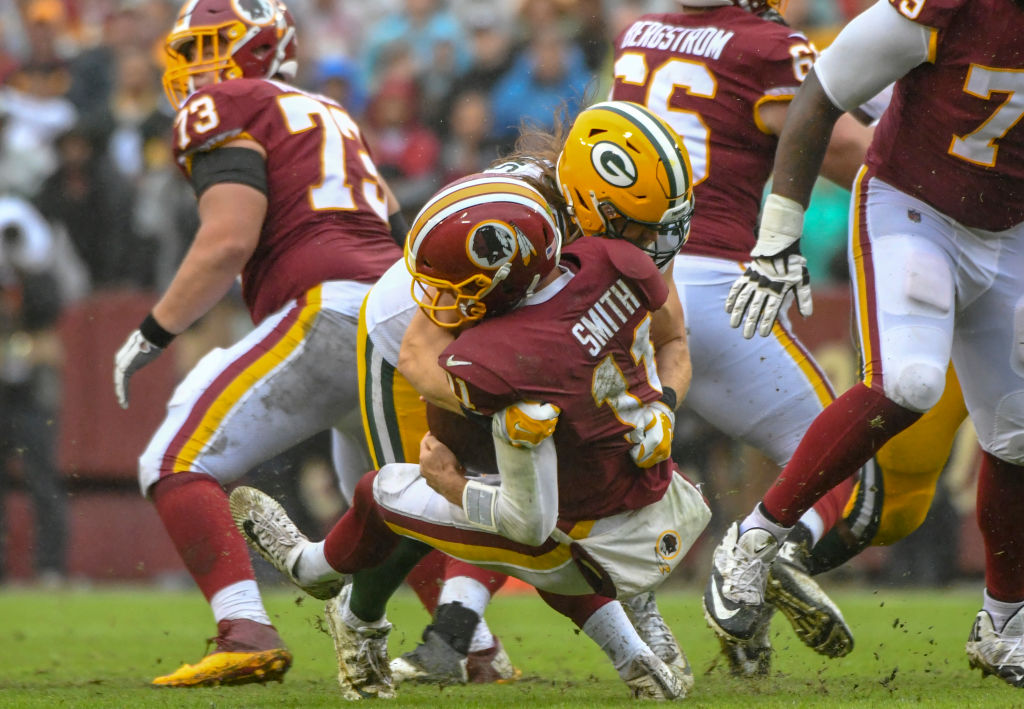 LANDOVER, MD - SEPTEMBER 23: Washington Redskins quarterback Alex Smith (11) is tackled by Green Bay Packers linebacker Clay Matthews (52) who was called for roughing the passer in the fourth quarter on September 23, 2018, at FedEx Field in Landover, MD. The Washington Redskins defeated the Green Bay Packers, 31-17