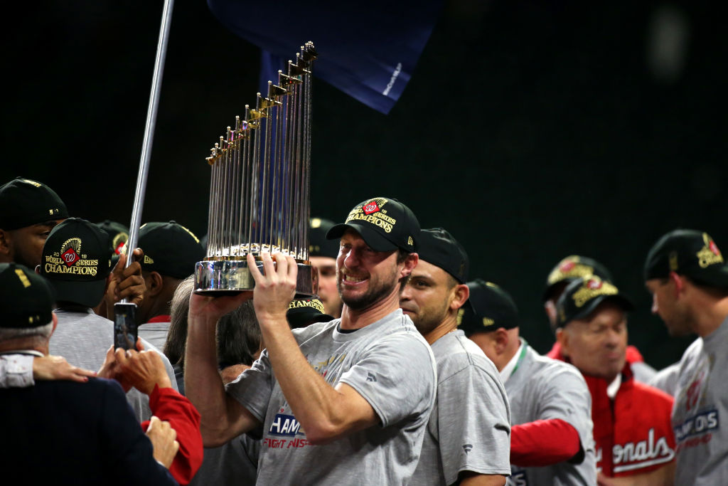 HOUSTON, TX - OCTOBER 30: Max Scherzer #31 of the Washington Nationals celebrates with the Commissioner's Trophy alongside teammates after the Nationals defeated the Houston Astros in Game 7 to win the 2019 World Series at Minute Maid Park on Wednesday, October 30, 2019 in Houston, Texas