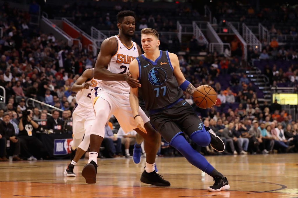PHOENIX, ARIZONA - DECEMBER 13: Luka Doncic #77 of the Dallas Mavericks drives the ball past Deandre Ayton #22 of the Phoenix Suns during the NBA game at Talking Stick Resort Arena on December 13, 2018 in Phoenix, Arizona