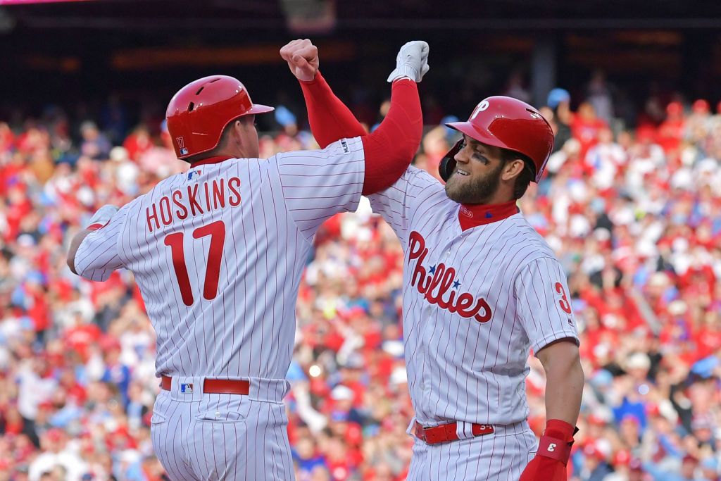 PHILADELPHIA, PA - MARCH 28: Rhys Hoskins #17 and Bryce Harper #3 of the Philadelphia Phillies celebrate Hoskins grand slam in the seventh inning against the Atlanta Braves on Opening Day at Citizens Bank Park on March 28, 2019 in Philadelphia, Pennsylvania