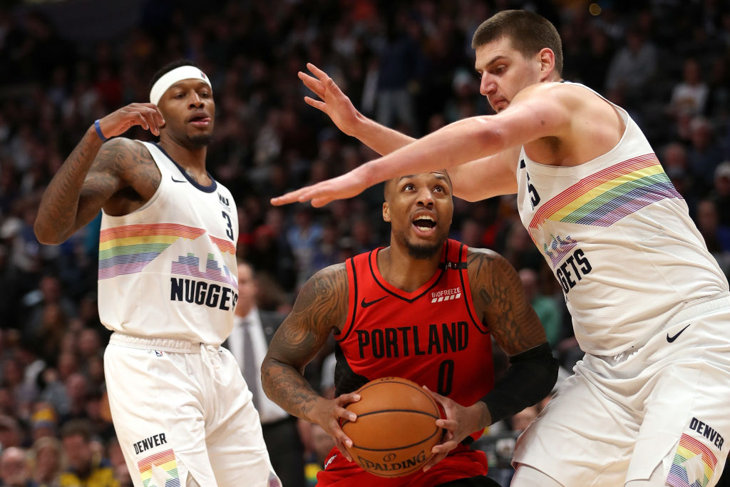 DENVER, COLORADO - JANUARY 13: Damian Lillard #0 of the Portland Trail Blazers drives against Nikola Jokic #15 of the Denver Nuggets at the Pepsi Center on January 13, 2019 in Denver, Colorado. NOTE TO USER: User expressly acknowledges and agrees that, by downloading and or using this photograph, User is consenting to the terms and conditions of the Getty Images License Agreement.