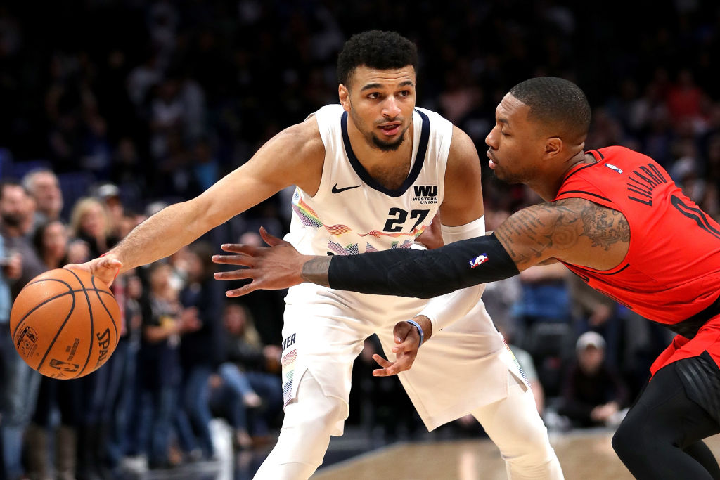 DENVER, COLORADO - JANUARY 13: Jamal Murray #27 of the Denver Nuggets is guarded by Damian Lillard #0 the Portland Trail Blazers in the first quarter at the Pepsi Center on January 13, 2019 in Denver, Colorado. NOTE TO USER: User expressly acknowledges and agrees that, by downloading and or using this photograph, User is consenting to the terms and conditions of the Getty Images License Agreement.