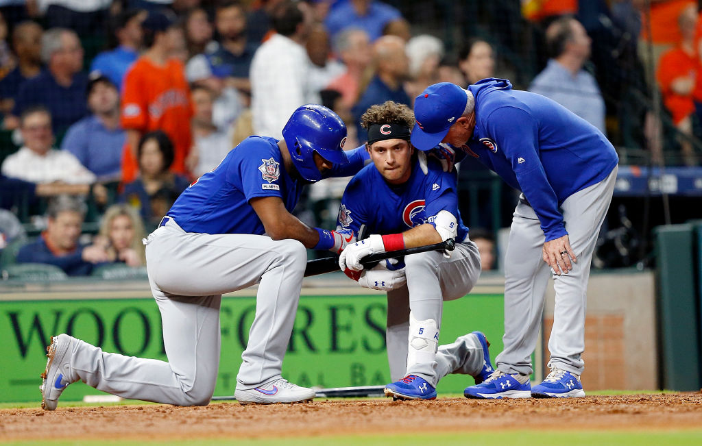 HOUSTON, TEXAS - MAY 29: Albert Almora Jr. #5 of the Chicago Cubs is comforted by manager Joe Maddon #70 and Jason Heyward #22 after a young child was injured on foul ball off his bat in the fourth inning against the Houston Astros at Minute Maid Park on May 29, 2019 in Houston, Texas