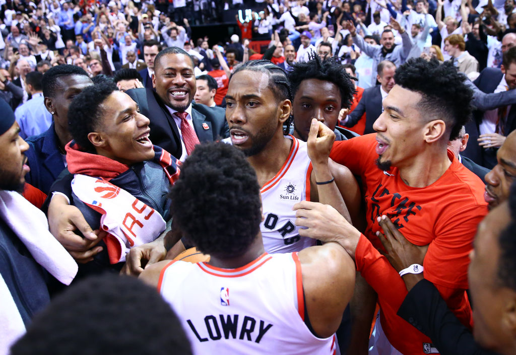TORONTO, ON - MAY 12: Kawhi Leonard #2 of the Toronto Raptors celebrates with teammates after sinking a buzzer beater to win Game Seven of the second round of the 2019 NBA Playoffs against the Philadelphia 76ers at Scotiabank Arena on May 12, 2019 in Toronto, Canada.