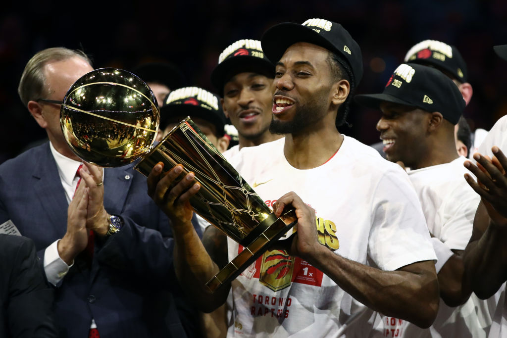 OAKLAND, CALIFORNIA - JUNE 13: Kawhi Leonard #2 of the Toronto Raptors celebrates with the Larry O'Brien Championship Trophy after his team defeated the Golden State Warriors to win Game Six of the 2019 NBA Finals at ORACLE Arena on June 13, 2019 in Oakland, California.