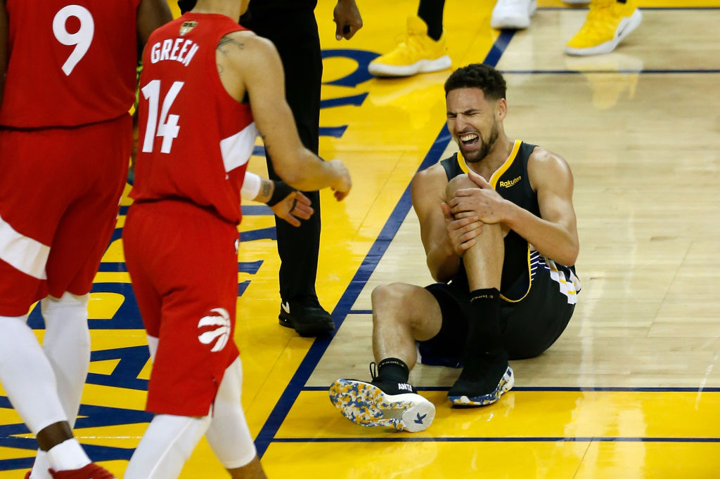 OAKLAND, CALIFORNIA - JUNE 13: Klay Thompson #11 of the Golden State Warriors reacts after hurting his leg against the Toronto Raptors in the second half during Game Six of the 2019 NBA Finals at ORACLE Arena on June 13, 2019 in Oakland, California
