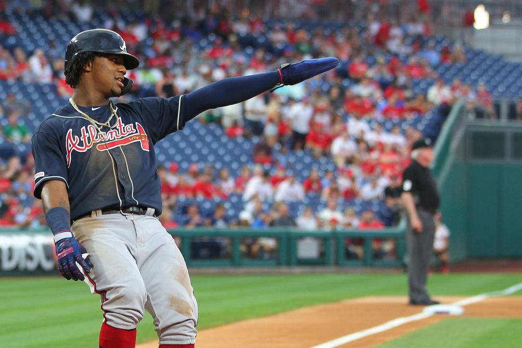 PHILADELPHIA, PA - JULY 26: Ronald Acuna Jr. #13 of the Atlanta Braves gestures to Freddie Freeman #5 after scoring on Freeman's single during the first inning of a game at Citizens Bank Park on July 26, 2019 in Philadelphia, Pennsylvania