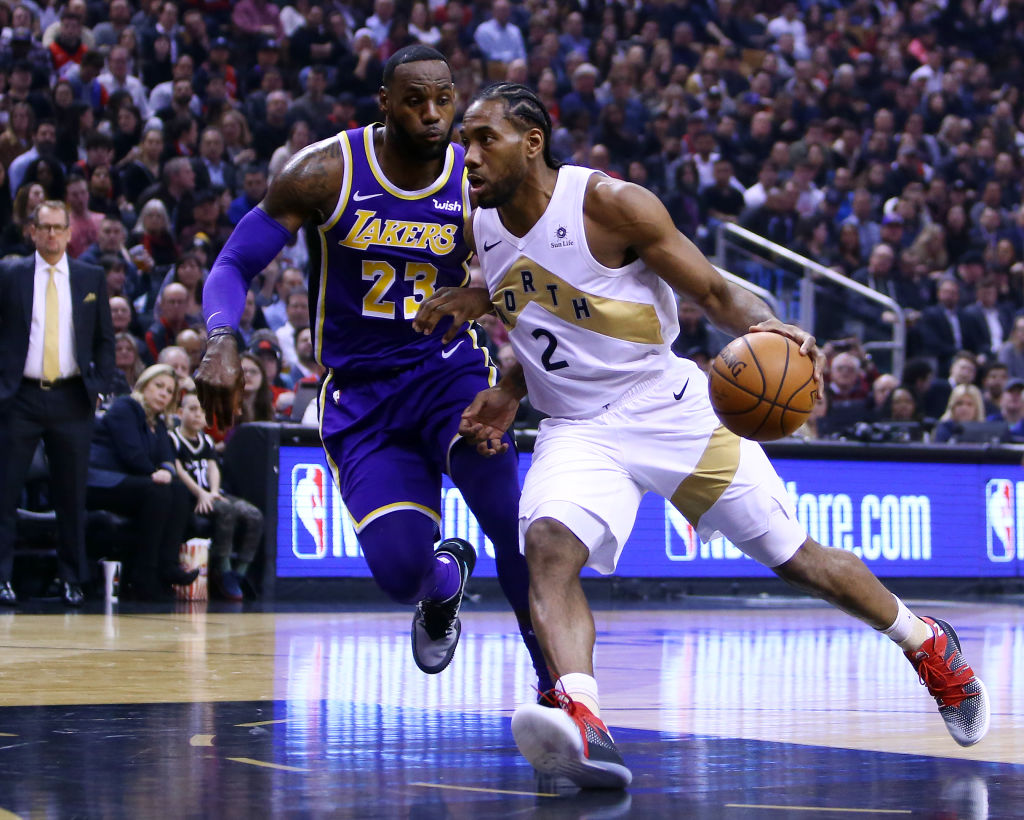TORONTO, ON - MARCH 14: Kawhi Leonard #2 of the Toronto Raptors dribbles the ball as LeBron James #23 of the Los Angeles Lakers defends during the first half of an NBA game at Scotiabank Arena on March 14, 2019 in Toronto, Canada.