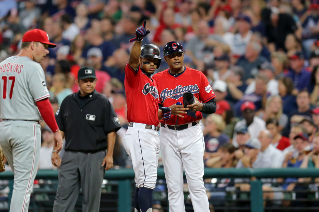 CLEVELAND, OH - SEPTEMBER 20: Cleveland Indians shortstop Francisco Lindor (12) motions to the Indians dugout as he stands at first base with Cleveland Indians first base coach Sandy Alomar Jr. (15) after driving in a run with a single during the second inning of the Major League Baseball interleague game between the Philidelphia Phillies and Cleveland Indians on September 20, 2019, at Progressive Field in Cleveland, OH