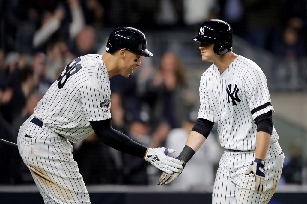 NEW YORK, NEW YORK - OCTOBER 04: DJ LeMahieu #26 of the New York Yankees celebrates with teammate Aaron Judge #99 after scoring a solo home run against Cody Stashak #61 of the Minnesota Twins during the sixth inning in game one of the American League Division Series at Yankee Stadium on October 04, 2019 in New York City