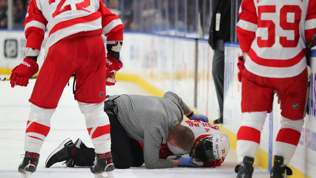 Red Wings head athletic therapist Piet Van Zant attends to forward Brendan Perlini after Perlini was hit by an errant skate to the face in the first period against the Buffalo Sabres at KeyBank Center on February 11, 2020 in Buffalo, New York