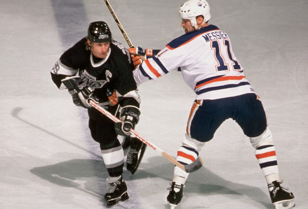 Canadian professional hockey player Wayne Gretzky (left), center for the Los Angeles Kings, is checked by Canadian professional hockey player Mark Messier, center for the Edmonton Oilers, during a game at Northlands Coliseum (now Rexall Place), Edmonton, Alberta, Canada, late 1980s.