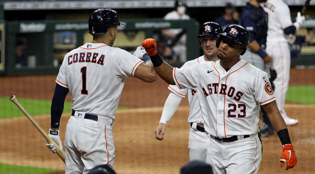 HOUSTON, TEXAS - JULY 24: Michael Brantley #23 of the Houston Astros is congratulated by Carlos Correa #1 and Alex Bregman #2 after hitting a three run home run in the fifth inning against the Seattle Mariners during Opening Day at Minute Maid Park on July 24, 2020 in Houston, Texas. The 2020 season had been postponed since March due to the COVID-19 pandemic.