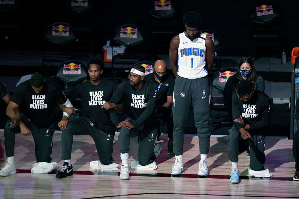 LAKE BUENA VISTA, FL - JULY 31: Jonathan Isaac #1 of the Orlando Magic stands as others kneel before the start of a game between the Brooklyn Nets and the Orlando Magic on July 31, 2020 at The HP Field House at ESPN Wide World Of Sports Complex in Lake Buena Vista, Florida