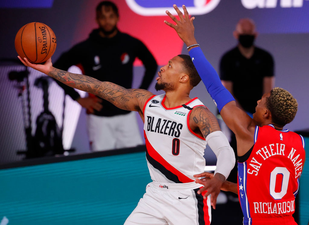 LAKE BUENA VISTA, FLORIDA - AUGUST 09: Damian Lillard #0 of the Portland Trail Blazers goes up for a shot against Josh Richardson #0 of the Philadelphia 76ers at Visa Athletic Center at ESPN Wide World Of Sports Complex on August 09, 2020 in Lake Buena Vista, Florida
