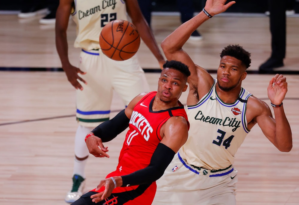 LAKE BUENA VISTA, FLORIDA - AUGUST 02: Russell Westbrook #0 of the Houston Rockets passes under pressure from Giannis Antetokounmpo #34 of the Milwaukee Bucks at The Arena at ESPN Wide World Of Sports Complex on August 02, 2020 in Lake Buena Vista, Florida