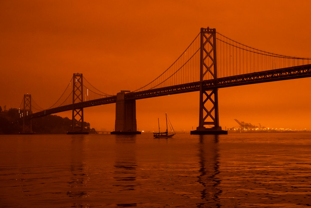 SAN FRANCISCO, CA - SEPTEMBER 09: A ship passes beneath the Bay Bridge as smoke from various wildfires burning across Northern California mixes with the marine layer, blanketing San Francisco in darkness and an orange glow on September 9, 2020 in San Francisco, California. Over 2 million acres have burned this year as wildfires continue to burn across the state