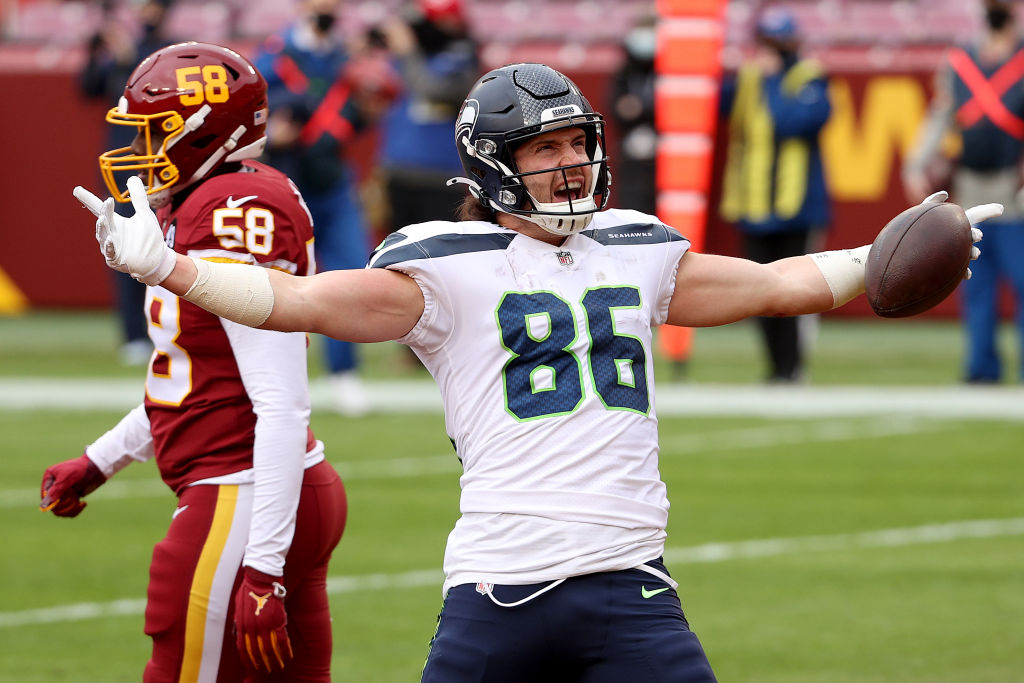 LANDOVER, MARYLAND - DECEMBER 20: Tight end Jacob Hollister #86 of the Seattle Seahawks celebrates in front of outside linebacker Thomas Davis #58 of the Washington Football Team after catching a first half touchdown pass at FedExField on December 20, 2020 in Landover, Maryland