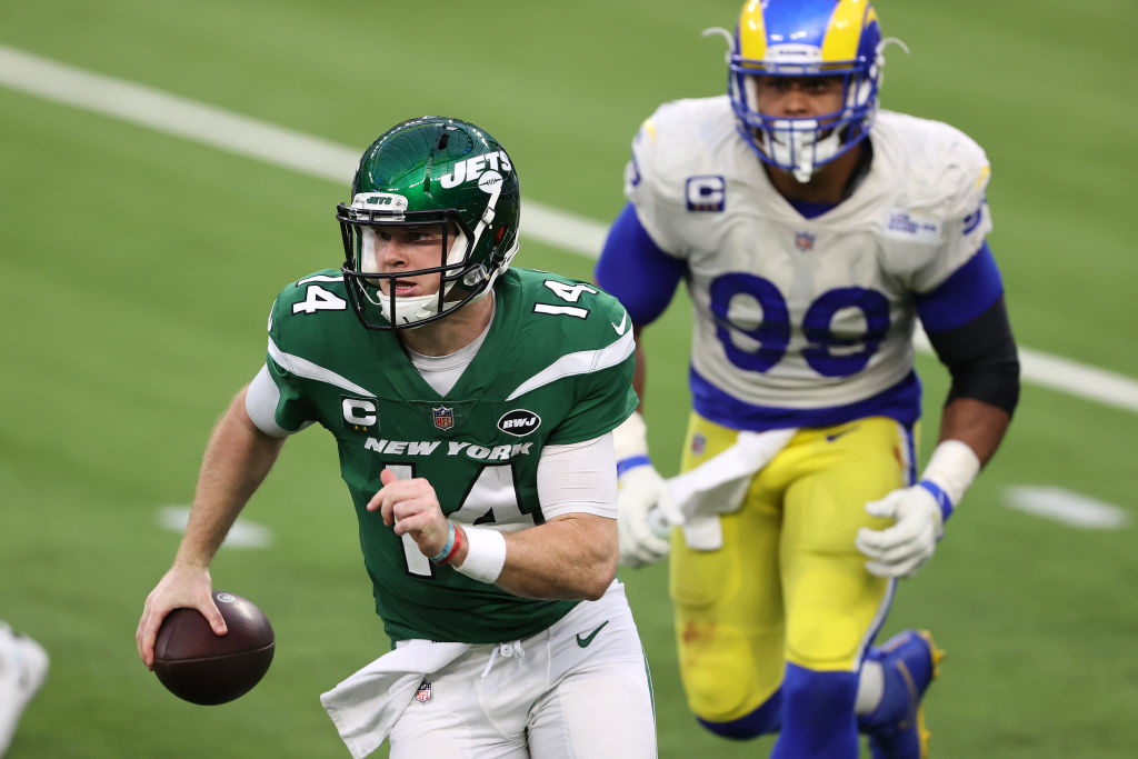 INGLEWOOD, CALIFORNIA - DECEMBER 20: Sam Darnold #14 of the New York Jets scrambles out of the pocket as Aaron Donald #99 of the Los Angeles Rams defends during the second half of a game at SoFi Stadium on December 20, 2020 in Inglewood, California