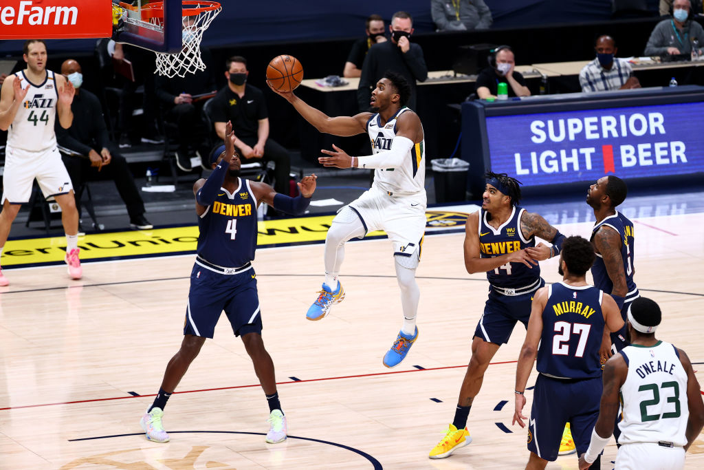 DENVER, CO - JANUARY 17: Donovan Mitchell #45 of the Utah Jazz drives to the hoop in the second quarter against Paul Millsap #4 of the Denver Nuggets at Ball Arena on January 17, 2021 in Denver, Colorado