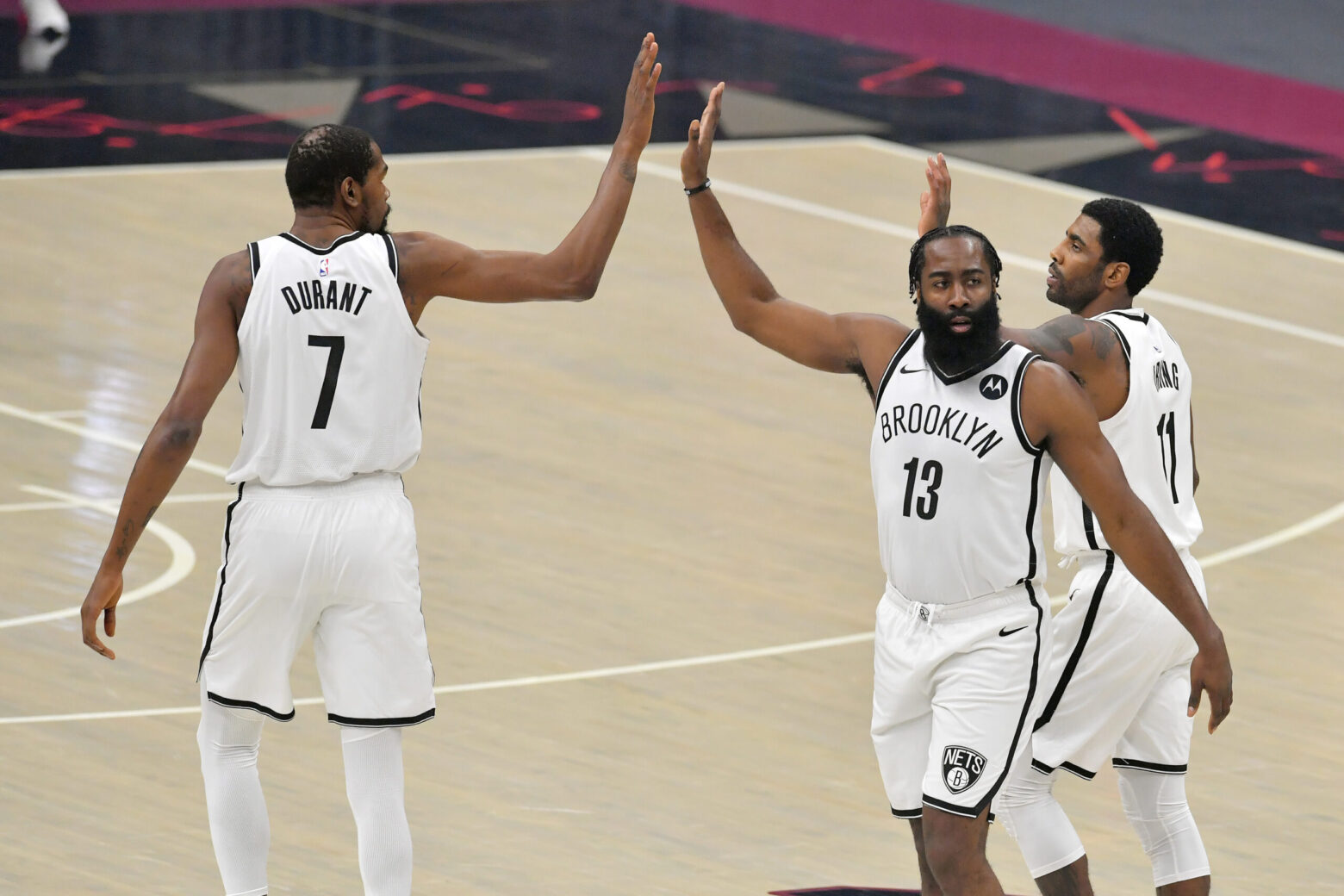 CLEVELAND, OHIO - JANUARY 20: Kevin Durant #7 James Harden #13 and Kyrie Irving #11 of the Brooklyn Nets celebrate during the first quarter against the Cleveland Cavaliers at Rocket Mortgage Fieldhouse on January 20, 2021 in Cleveland, Ohio