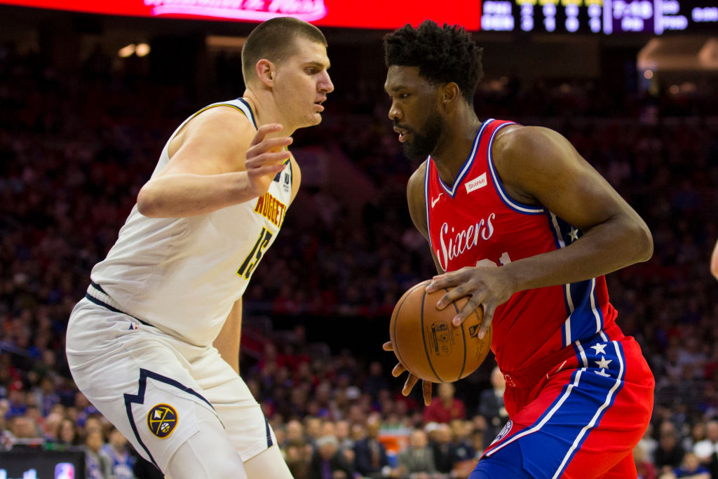 PHILADELPHIA, PA - FEBRUARY 08: Joel Embiid #21 of the Philadelphia 76ers controls the ball against Nikola Jokic #15 of the Denver Nuggets at the Wells Fargo Center on February 8, 2019 in Philadelphia, Pennsylvania. The 76ers defeated the Nuggets 117-110