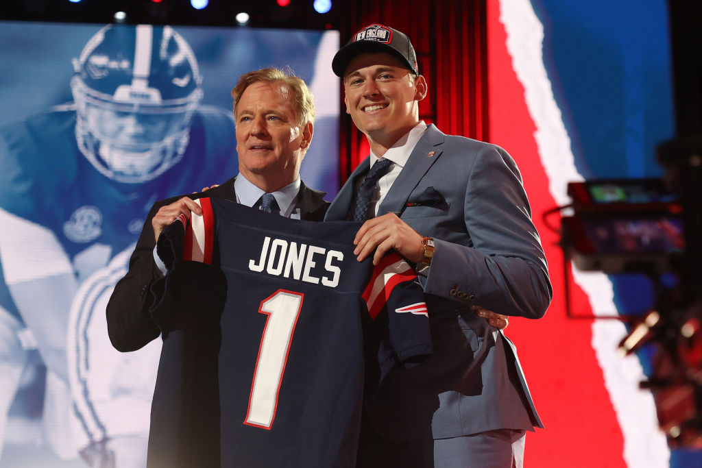 CLEVELAND, OHIO - APRIL 29: Mac Jones poses with NFL Commissioner Roger Goodell onstage after being selected 15th by the New England Patriots during round one of the 2021 NFL Draft at the Great Lakes Science Center on April 29, 2021 in Cleveland, Ohio