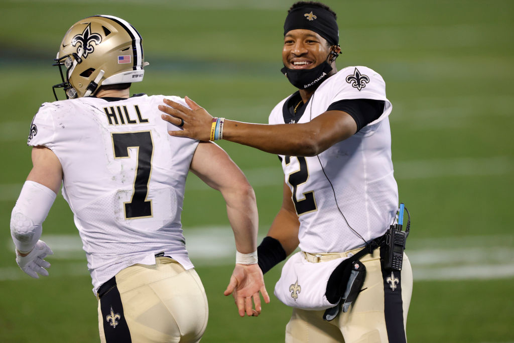 CHARLOTTE, NORTH CAROLINA - JANUARY 03: Quarterback Jameis Winston #2 of the New Orleans Saints shares a smile as he greets teammate quarterback Taysom Hill #7 during the second half of their game against the Carolina Panthers at Bank of America Stadium on January 03, 2021 in Charlotte, North Carolina