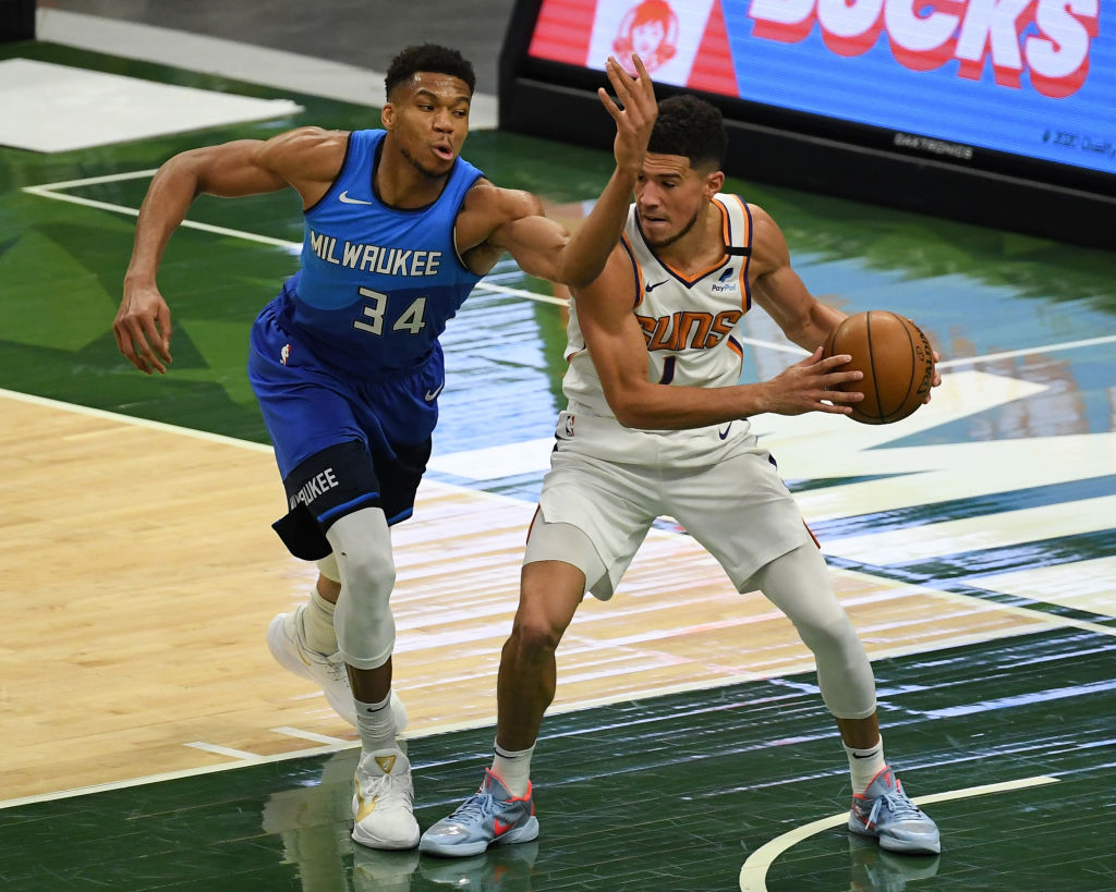 MILWAUKEE, WISCONSIN - APRIL 19: Giannis Antetokounmpo #34 of the Milwaukee Bucks attempts a steal against Devin Booker #1 of the Phoenix Suns in the third quarter at Fiserv Forum on April 19, 2021 in Milwaukee, Wisconsin