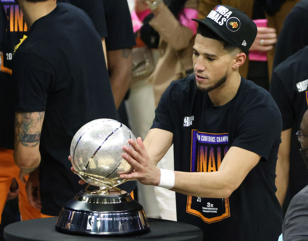 LOS ANGELES, CALIFORNIA - JUNE 30: Devin Booker #1 of the Phoenix Suns holds the Western Conference Championship trophy after the Suns defeated the LA Clippers in Game Six of the Western Conference Finals at Staples Center on June 30, 2021 in Los Angeles, California
