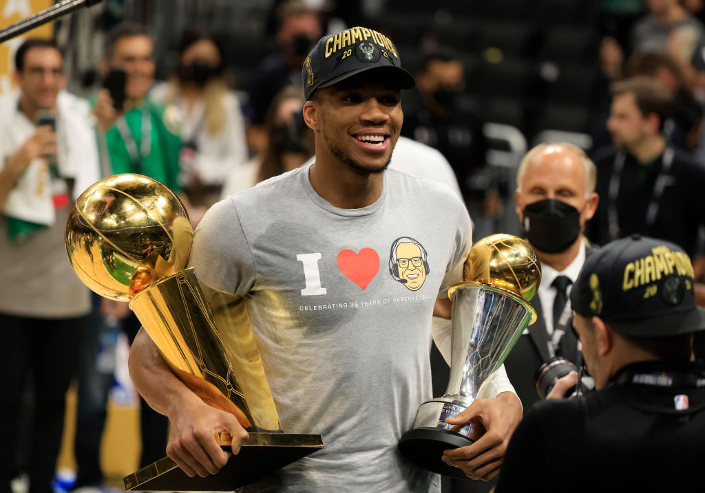 MILWAUKEE, WISCONSIN - JULY 20: Giannis Antetokounmpo #34 of the Milwaukee Bucks holds the Bill Russell NBA Finals MVP Award and the Larry O'Brien Championship Trophy after defeating the Phoenix Suns in Game Six to win the 2021 NBA Finals at Fiserv Forum on July 20, 2021 in Milwaukee, Wisconsin