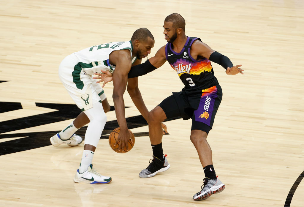 PHOENIX, ARIZONA - FEBRUARY 10: Khris Middleton #22 of the Milwaukee Bucks handles the ball against Chris Paul #3 of the Phoenix Suns during the NBA game at Phoenix Suns Arena on February 10, 2021 in Phoenix, Arizona. The Suns defeated the Bucks 125-124.